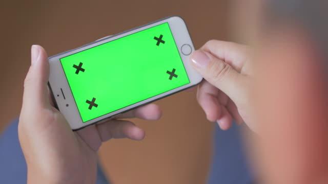 Över axeln smart skott av använda telefon, grön skärm