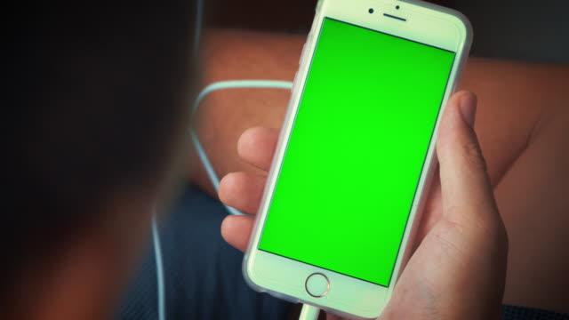 Indietro di utilizzo di uno smartphone, schermo verde