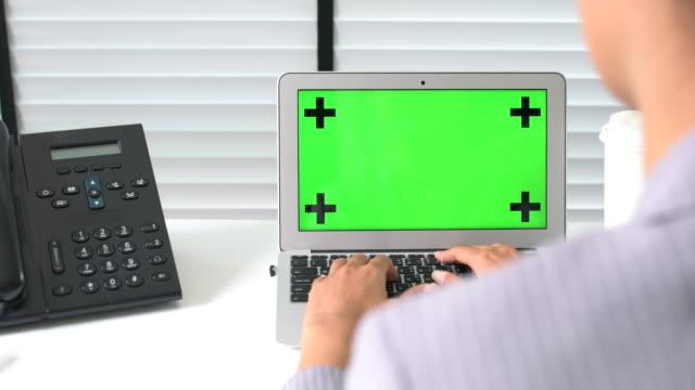 De weergave van de schouder van zakenvrouw zit op haar Bureau en werken op een Laptop met groen scherm
