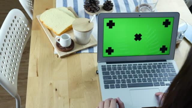 Over the Shoulder view of Woman Using Laptop with Green screen with Breakfast, Chroma key