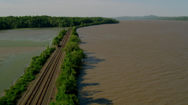 WIDE AERIAL POV over train tracks on causeway over Hudson River in rural area