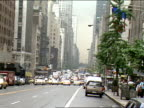 overcast summer day LS ZI WS Busy twoway multilane street in Manhattan cars cabs and buses driving office buildings along street and skyscrapers in BG