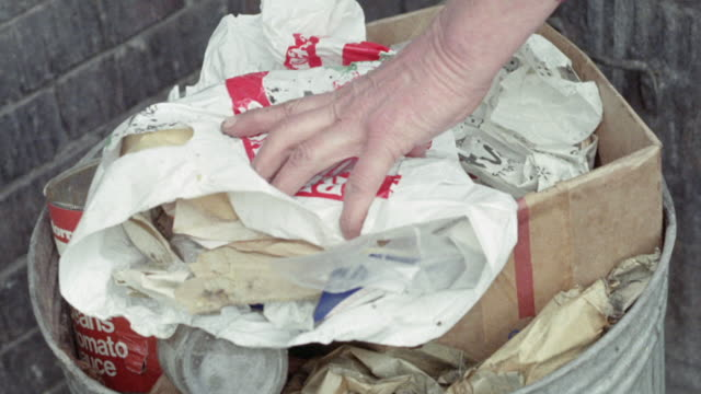 1973 MONTAGE Overflowing garbage cans and workers emptying cans into truck / United Kingdom