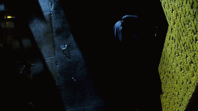 WS Overhead - man in hoodie walks to door in dark alleyway. The door opens spilling light into the alleyway, and he enters.