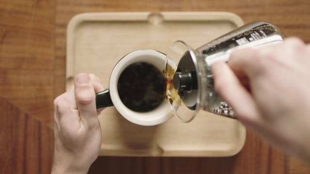 Overhead plating shot as hands pour coffee from pot into mug on wooden tray in coffee shop.