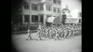 Overhead shot of Liberian soldiers marching in formation past awning at entrance of the Executive Mansion / Tubman and official on his right and two...