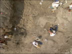 Overhead shot of workers digging in fossil bed for T. rex bones / Hell Creek, Montana