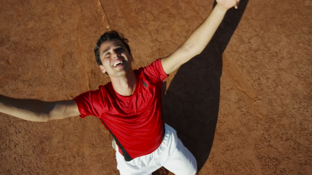 Overhead slow motion shot of joyful man on his knees on clay tennis court, pointing and cheering in celebration