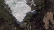 AERIAL. Overhead view as ocean water spills and crashes over rocky island shore.