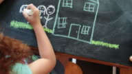 Overhead view, young girl drawing a house and family with chalk on a table