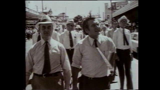 NATSOT overlay ACTU President Bob Hawke shirt sleeves rolled up leading street march with other unionists / close up smiling laughing and waving /...