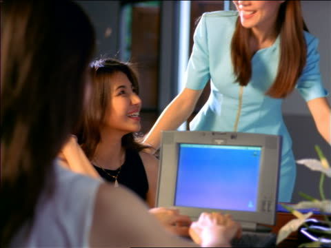 REAR VIEW over-the-shoulder Asian woman uses laptop + talks to other Asian woman / a third joins them / Thailand