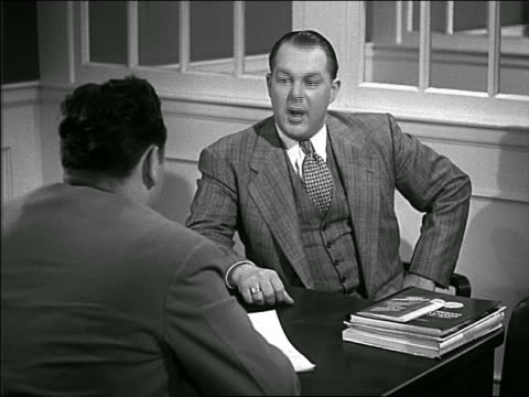 B/W 1949 over-the-shoulder man in suit sitting at desk being interview by other man