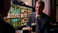 over-the-shoulder two businessmen sit at table next to window in pub, drinking beer + talking / Dublin, Ireland