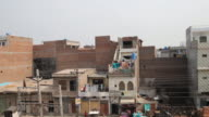 Overview of residential area in Lahore with laundry drying on balconies at prayer time