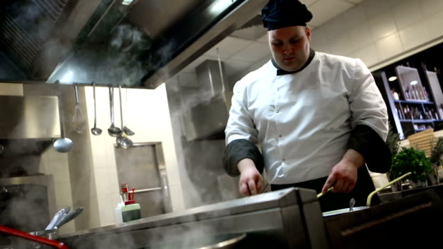 Overweight male chef cooking in a restaurant.