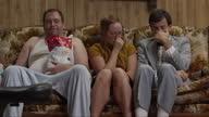 MS TU Overweight  man wearing pajamas, holding bag of chips sitting by nerdy couple on sofa / Orem, Utah, USA