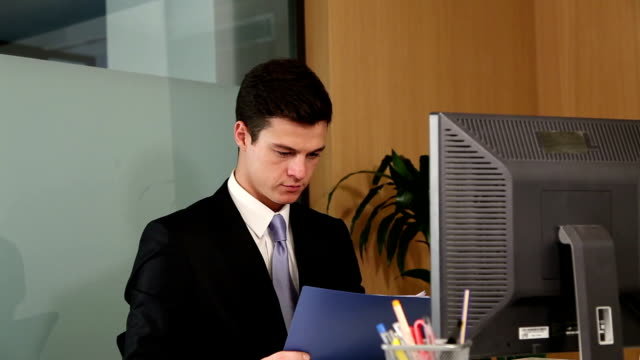 Overworked businessman sighs after seeing what work he has left