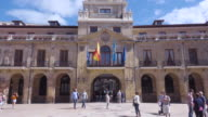 4K | Oviedo city council builinding. Ayuntamiento of the city with big square. People are having a walk at this sunny day. Local and Spanish flags wave