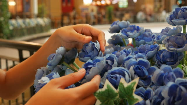 owner flower shop arranging blue bouquet