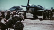 Oxcart full of US Marines passing P47 Thunderbolt pilot and ground crew during WWII