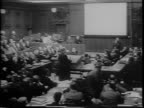 Packed courtroom/ men sit at tiered tables many with headphones / soldiers in uniform along the walls in back / men with headphones at desk /...