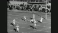 Packed crowd at Harvard Stadium for football game between Boston Patriots and the Buffalo Bills / game begins / several plays shown / CU scoreboard /...