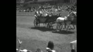 PAN packed stands at Ascot / PAN carriage with royal family George V Queen Mary Prince Edward Prince Henry / woman walking in diaphanous dress /...