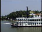 Paddle steamer sails from right to left along Mississippi river paddle turning at rear