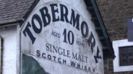 CU Painted sign on wall of Tobermory Distillery advertising whiskey / Tobermory, Scotland, United Kingdom