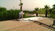 WS Painter on roof spraying roof shingles / Rancho Mirage, California, USA.