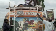ECU Painting of Saint George on his horse on back of truck as it drives away on busy street / Port-au-Prince, Haiti