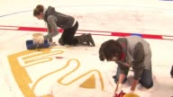 WGN painting the Indian head logo and line on the Chicago Blackhawks' home ice rink at the United Center on Sept 21 2016