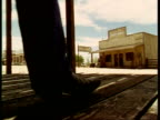 Pair of Cowboy boots walk past and away from camera, left to right, Western town, USA