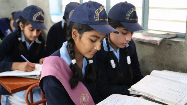 Pair of girls wearing school caps learn together In the background the rest of the class do the same