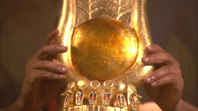 A pair of hands places a gold crown with wings on the head of cleopatra.