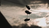 A pair of sneakers hanging over a telephone line at sunset