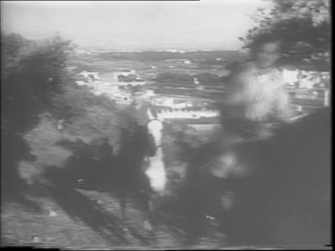 A pair of soldiers on horseback ride in the hills near Rome / soldiers mill about in front of a large US Army Rest Center / soldiers ice skate in...