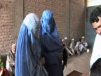 Pair of women traditional burqa clothing register at relief centre following severe rains and flooding in Pakistan