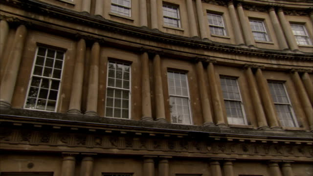 Pairs of Corinthian pilasters divide curving rows of townhouses forming The Circus in Bath, England. Available in HD.