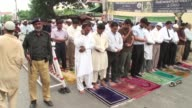 Pakistani Muslims offer Friday prayer outside the local mosque at I I Chundrigar Road a financial district of Karachi Pakistan A Pakistani policeman...