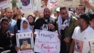 Palestinian protestors hold banners during a demonstration in support of the Palestinian prisoners held in Israeli jails outside the Mahd Church as...