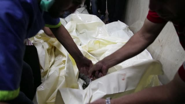 Palestinian volunteers at Gaza Citys al Shifa hospital load body bags with the remains of children on stretchers after an Israeli air strike in Gaza...