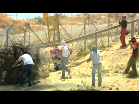 Palestinian youths attempt to destroy barbed wire maintaining Israeli border 5 August 2009