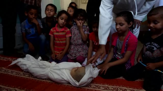 Palestinians buried the dead including fivemonth old girl Lama al Satri who was killed with two other men in an Israeli air raid the previous day in...
