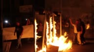 Palestinians burn mock metal detectors at the entrance to Bethlehem during a demonstration to protest Israeli violations against AlAqsa Mosque on...