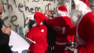 Palestinians dressed up as Santa Claus demonstrate in front of the Israeli separation wall during a protest in the West Bank city of Bethlehem 18...