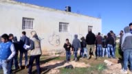 Palestinians inspect a spraypainting Hebrew graffiti on a Paletinian family's house attacked by Jewish extremists on December 22 2015 in the West...
