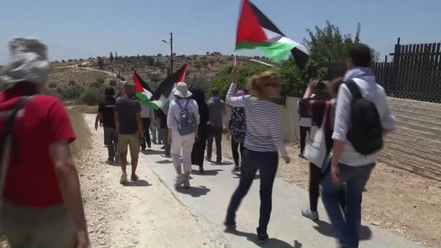 Palestinians march and shout slogans during a protest against the construction of Jewish settlement housing and the separation wall in the village of...