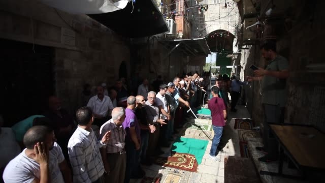 Palestinians perfrom afternoon prayer near the new security metal detectors outside one of the main entrances to the AlAqsa mosque refusing to enter...